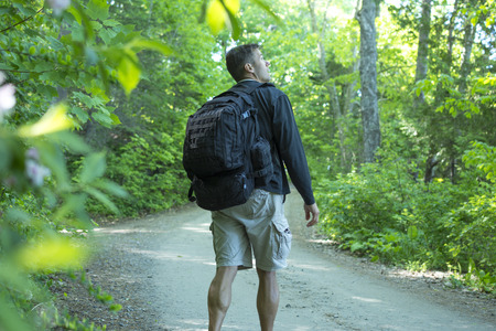 dirt road recreation: Male Caucasian hiker with big backpack and muscular calves walks on dirt road while looking up into trees of beautiful green northeast forest of Maine