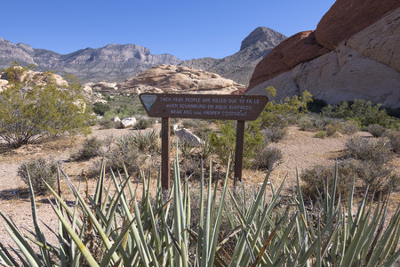 warns: Wooden sign warns hikers of falls on rocks at trailhead to Turtle Head Peak in Red Rock Canyon Nevada under sunny blue sky during spring Stock Photo