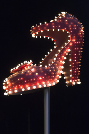 sin city: Famous silver slipper fully illuminated at night on top of pole on Fremont Street in Las Vegas on black sky background