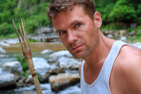 Closeup portrait of handsomely rugged Caucasian man with primitive bamboo spear in natural setting of jungle river environment