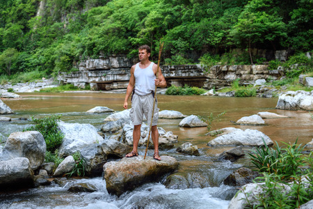 primal: Muscular adventurous Caucasian man in tank top and shorts holding spear while standing triumphantly on boulder in middle of river in tropical jungle in Chiapas, Mexico