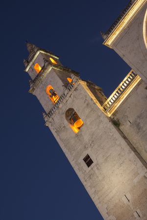 16th century: Beautifully illuminated exterior bell tower of 16th century Merida Cathedral in Yucatan, Mexico under dark blue twilight sky at night shot with tilted camera angle Editorial