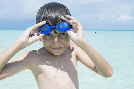 niño sin camisa: Primer del muchacho caucásico hermoso levantamiento azul gafas de natación, mientras que el goteo mojado de la natación en el mar tropical durante las vacaciones de verano