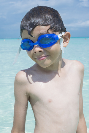 swim goggles: Closeup of handsome Caucasian boy wearing blue swim goggles and dripping wet from swimming in tropical sea under sunny sky while on summer vacation