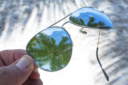 reveals: Closeup on lens of reflective sunglasses over sandy beach reveals reflections of tall coconut palms in tropical paradise