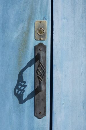 black shadow: Closeup and shadow of black iron door handle and brass key lock on exterior of blue wooden door in Valladolid, Mexico Stock Photo