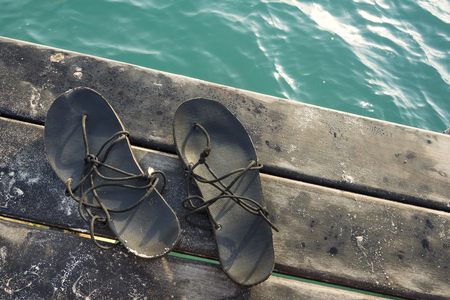 pier: High angle view of simple black primitive style sandals on edge of wooden dock scattered with fine sand next to blue green water illuminated by morning sun