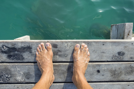 High angle POV of man's bare feet standing at edge of wooden dock sprinkled with fine white sand above aqua green sea water in natural morning light Stock Photo