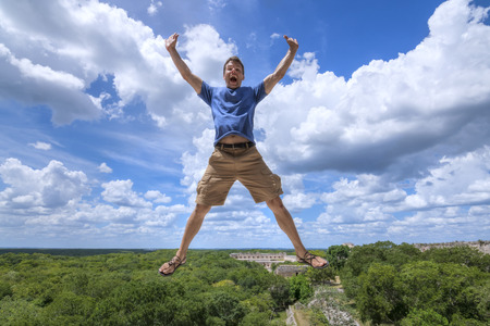 old man happy: Handsome Caucasian man airborne with arms outstretched while he shouts in joy over scenic landscape of Maya city Uxmal and jungle below Stock Photo