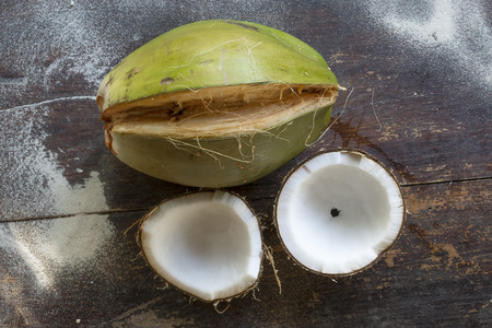 meaty: Big green coconut with husk partially peeled and two coconut halfs revealing white meaty interior on sandy wooden table
