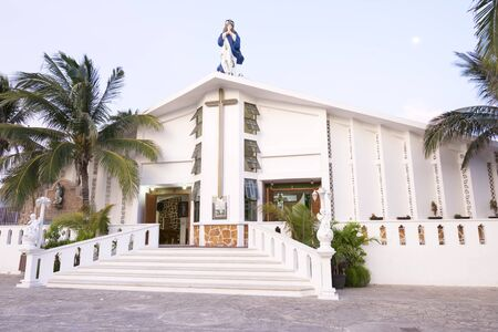 mujeres: Front exterior  entrance of Catholic church of the Immaculate Conception on Isla Mujeres with coconut palms in front at dusk