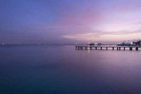 mujeres: Vividly colorful purple tinted Caribbean sunset over docks on Isla Mujeres island near Cancun, Mexico