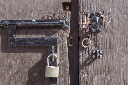 unlocked: Closeup of key padlock and unlocked metal rings on rustic weathered wooden door in natural exterior lighting