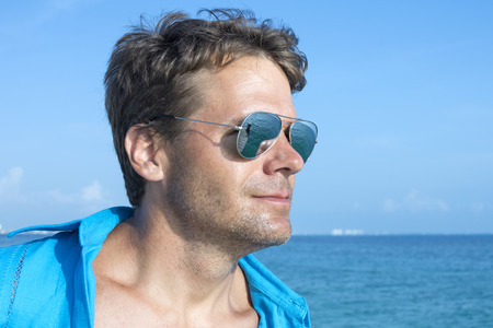 man looking: Closeup head shot of handsome Caucasian man wearing blue shirt and reflective sunglasses outdoors on sea under sunny sky