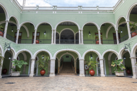 merida: Inside beautiful patio plaza of government palace in Merida, Mexico featuring colonial-style architecture with green and white painted walls, arches, tile flooring and potted tropical plants