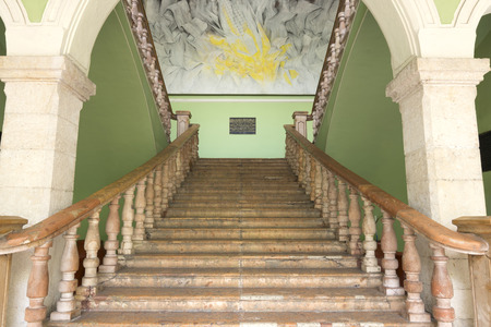 second floor: Beautiful old staircase leading to second floor of government palace in Merida, Mexico with famous painting by Fernando Castro Pacheco
