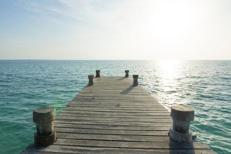 diminishing perspective: Diminishing perspective of wooden dock on calm sea illuminated by intense morning sunlight over horizon
