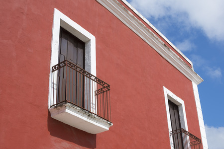 architectural exteriors: Closeup detail of upper corner of colorful colonial-style building in Valladolid, Mexico under sunny sky