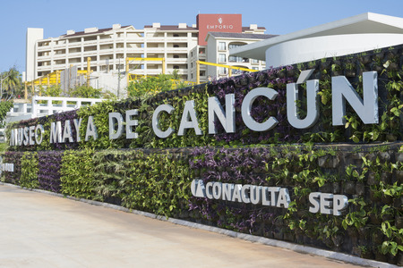 cancun: Attractive foliage covered wall with sign of the Mayan Museum of Cancun in large letters marking the entrance to the museum on the hotel zone