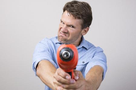 taladro: Hombre caucásico hermoso en la camisa azul hace contorsión facial agresiva mientras sostiene un taladro eléctrico como una pistola y le apunta a la cámara Foto de archivo