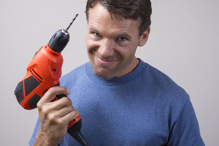 power drill: Closeup of handsome Caucasian man holding electric power drill with expression of readiness looking into camera