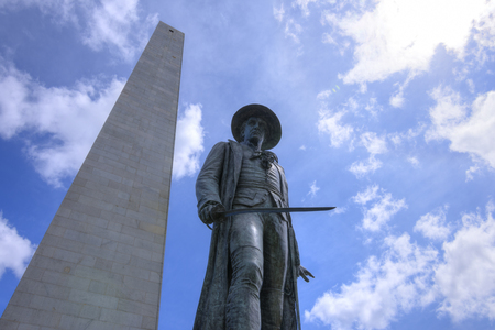 Low angle wide angle of Colonal William Prescott and Bunker Hill monument reaching high in the sunny sky of the Freedom Trail in Boston, Massachusetts Imagens