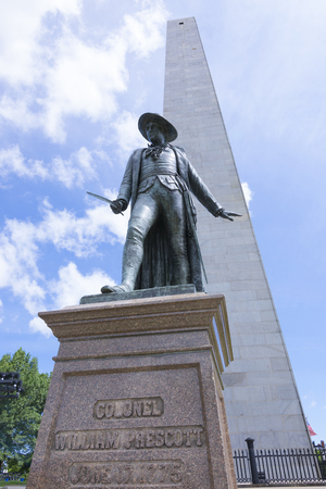 colonel: Low angle of statue dedicated to Colonel William Prescott with tall monument of Bunker Hill under sunny sky in Boston