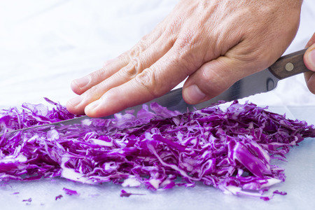 serrated: Closeup of hand pressing spine of serrated knife cutting small pieces of red cabbage in brightly lit kitchen
