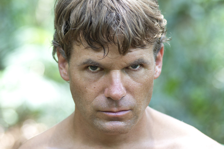 looking into camera: Closeup head shot of sweaty Caucasian man with serious bold expression looking into camera in wilderness surroundings