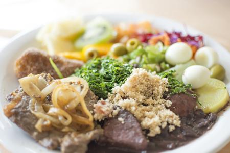 필드의 얕은 깊이와 고기로 구성된 브라질 전통 음식, 건조 유카, 검은 콩, 메추라기 계란과 야채의 확대 판