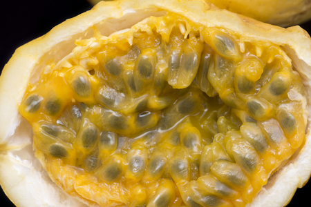 edulis: Macro closeup of cut in half yellow assiflora edulis var. flavicarpa passionfruit on black background