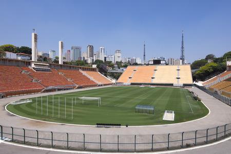 campo calcio: SAO PAULO, Brasile - 23 settembre 2015: tribune vuote e tappeto erboso verde del campo di calcio si siedono sotto un cielo azzurro pieno di sole e lo skyline di grattacieli alti di San Paolo a Paceambu Stadio Comunale Estdio Paulo Machado de Carvalho.