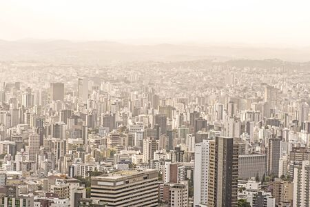 urbanized: Tall concrete buildings sprawl through heavily urbanized valley in Belo Horizonte, Minas Gerais, Brazil under hazy sky