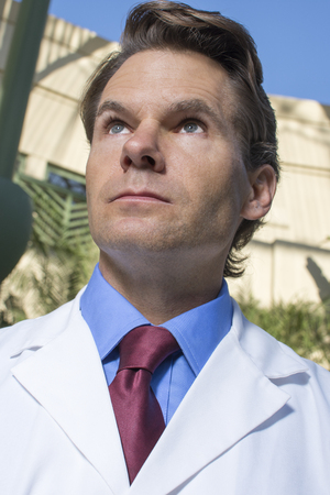 healthcare facilities: Low angle portrait of successful Caucasian doctor in white lab coat looking up outside of medical facility during day