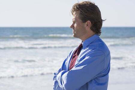 warm shirt: Frustrated and stressed out Caucasian office worker in blue shirt and red tie stands outdoors at beach in warm sunshine and thinks