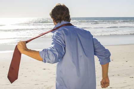 Caucasian businessman tearing off tie as he escapes the office and runs to beautiful beach on warm sunny day