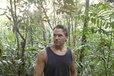 tank top: Handsome Caucasian man wearing black tank top surrounded by tropical vegetation as sunlight filters through jungle canopy
