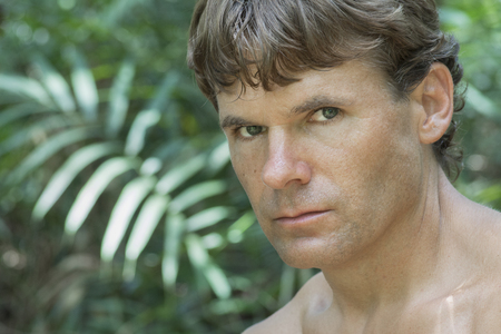 humid: Closeup portrait of handsome Caucasian man with intense eyes and serious bold expression in hot humid jungle environment Stock Photo
