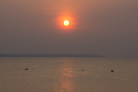 amazonas: Vermillion sunset penetrates hazy sky while reflecting over calm surface of Rio Negro at Ponta Negra near Manaus, Amazonas, Brazil