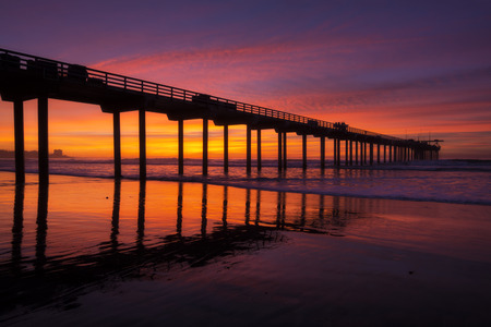 shores: Brilliant evening sunset and silhouette of Scripps Pier with reflections on La Jolla Shores beach in California