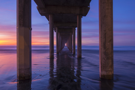 diminishing perspective: Diminishing center perspective of concrete columns under Scripps pier at beautiful sandy beach in La Jolla, CA during brilliant evening sunset
