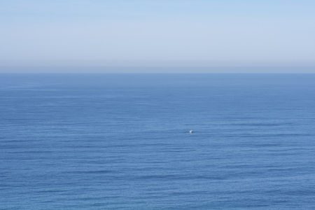 small boat: Small fishing vessel drifts in vast calm ocean under sunny sky Stock Photo