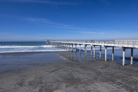 oceanography: Long concrete scientific pier at Scripps Institute of Oceanography in La Jolla, California extends far into beautiful ocean under clear blue sky at low tide Stock Photo