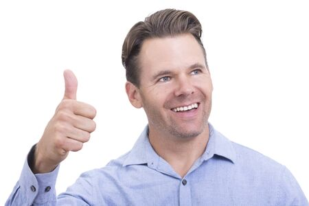 Handsome Caucasian man smiles and holds hand with one thumb up to celebrate success and optimisim on white background Imagens