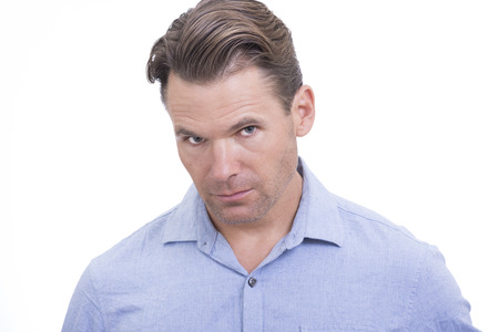 blank expression: Portrait of handsome Caucasian man with head tilted slightly down looking up at camera with blank expression on white background Stock Photo