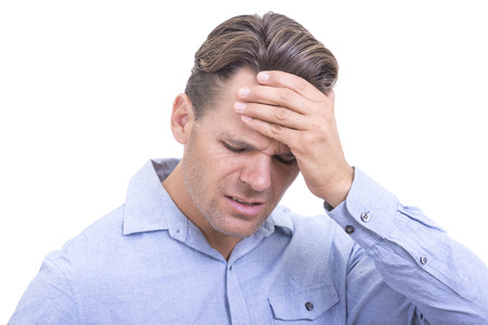 throb: Closeup of handsome Caucasian man wearing blue button down shirt and holding hand on head with look of frustration or suffering from painful headache on white background