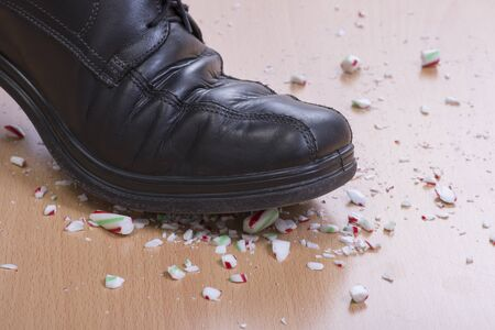 dress shoe: Closeup mans black dress shoe stepping onto and shattering Christimas candy cane on wood floor