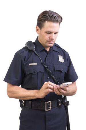 Guapo oficial de policía de raza caucásica en uniforme enviar el mensaje en el teléfono inteligente celular en el fondo blanco