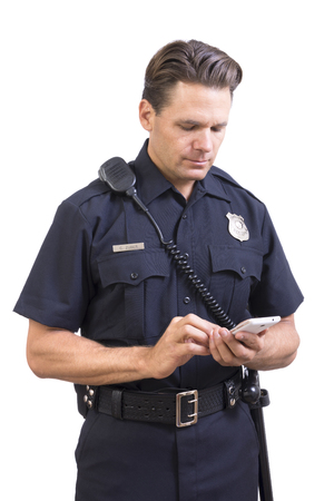 Handsome Caucasian police officer in uniform sending message on cellular smart phone on white background Stock Photo
