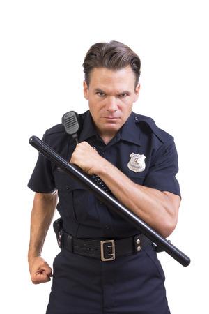 Hermoso serio oficial de policía de raza caucásica celebración bastón y carga hacia adelante agresivamente en el fondo blanco